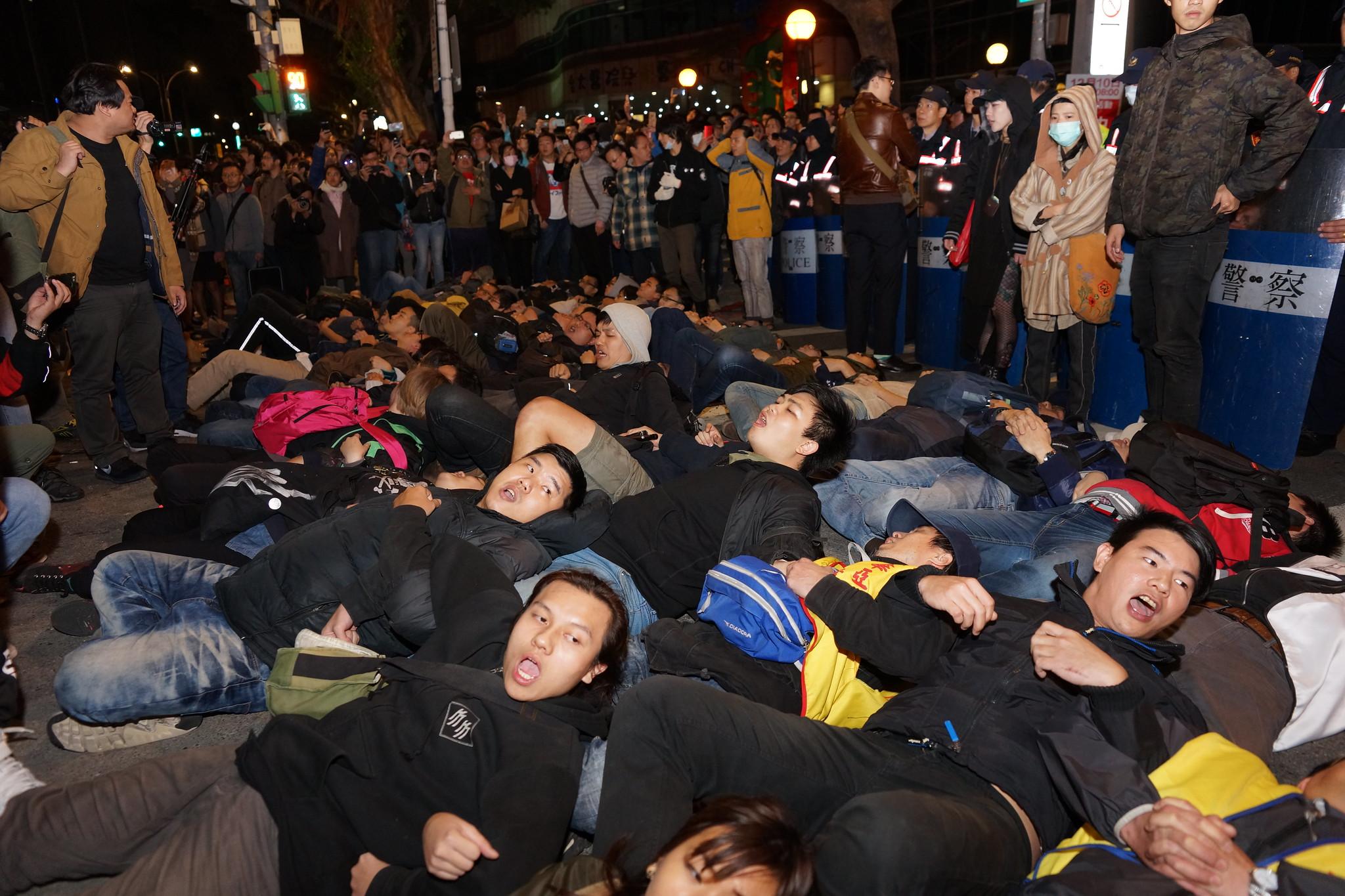 民眾以倒臥在路口,阻止警方的動作。(攝影:王顥中)
