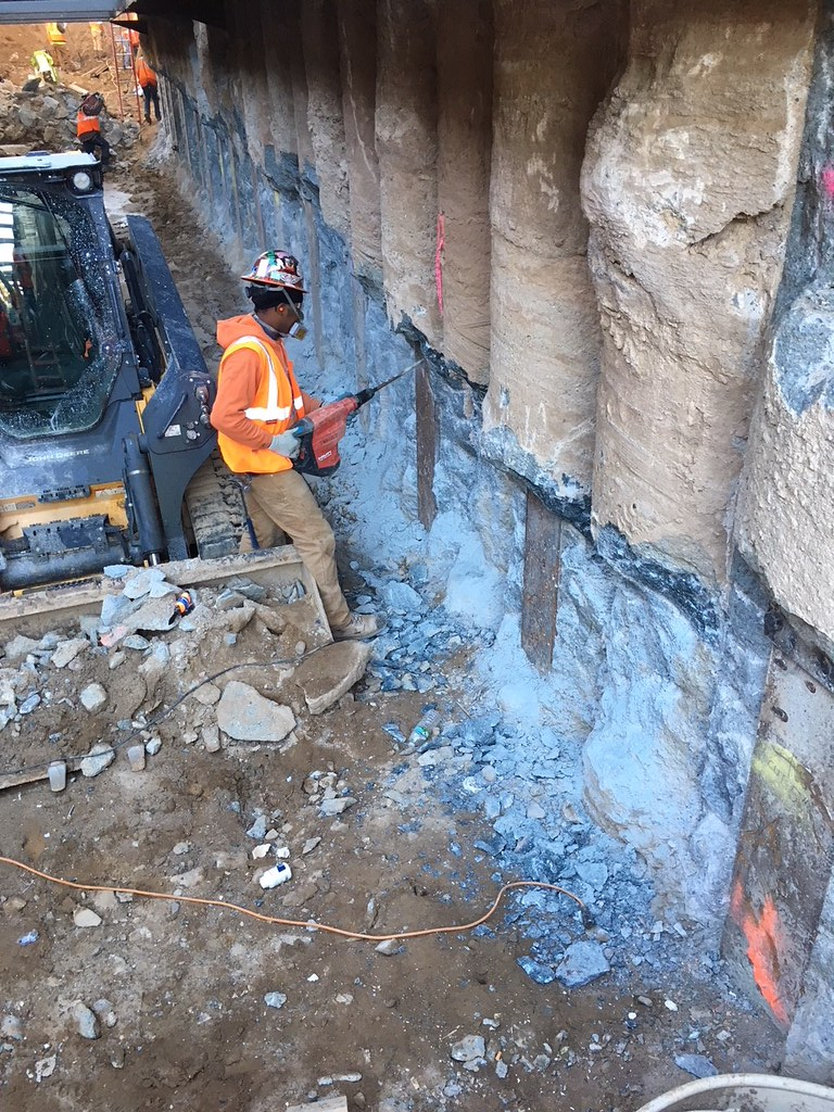 Chipping Concrete At The Base Of A Secant Pile Below The 3