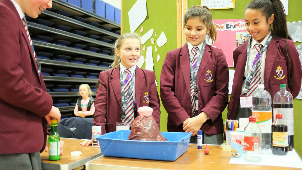 Four primary school girls stood around a paper mache volcana waiting for it to erupt as part of their science project