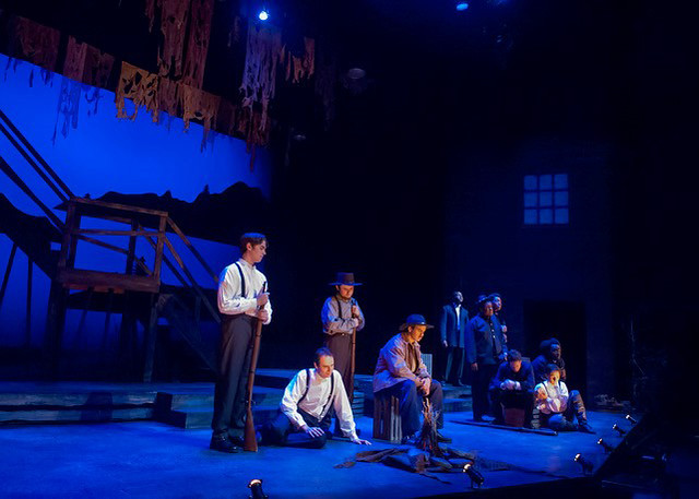 Male cast members is are kneeling, standing or sitting on stage