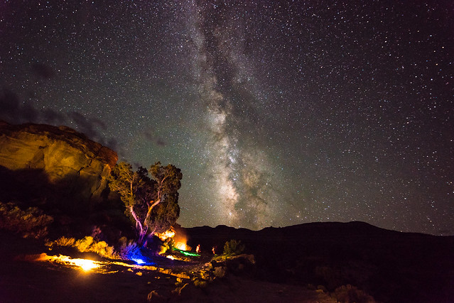 The Milky Way blazes through a star-filled sky, with a silhouetted mountain range below. In the foreground, tents and camp lights shine beneath a slickrock cliff and a tall pinon pine.