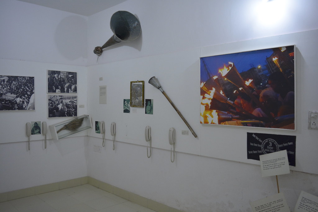 The upper level of the building has walls decked with torches, loudspeakers, banners, brooms and various other art forms used by protesters over the years to jolt the society out of its business-as-usual approach.