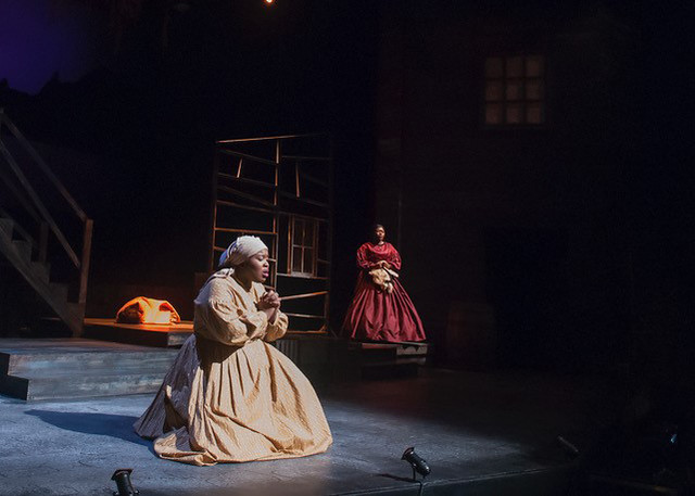 "A female cast member is on her knees praying during a production of ""A Civil War Christmas: An American Musical Celebration."""