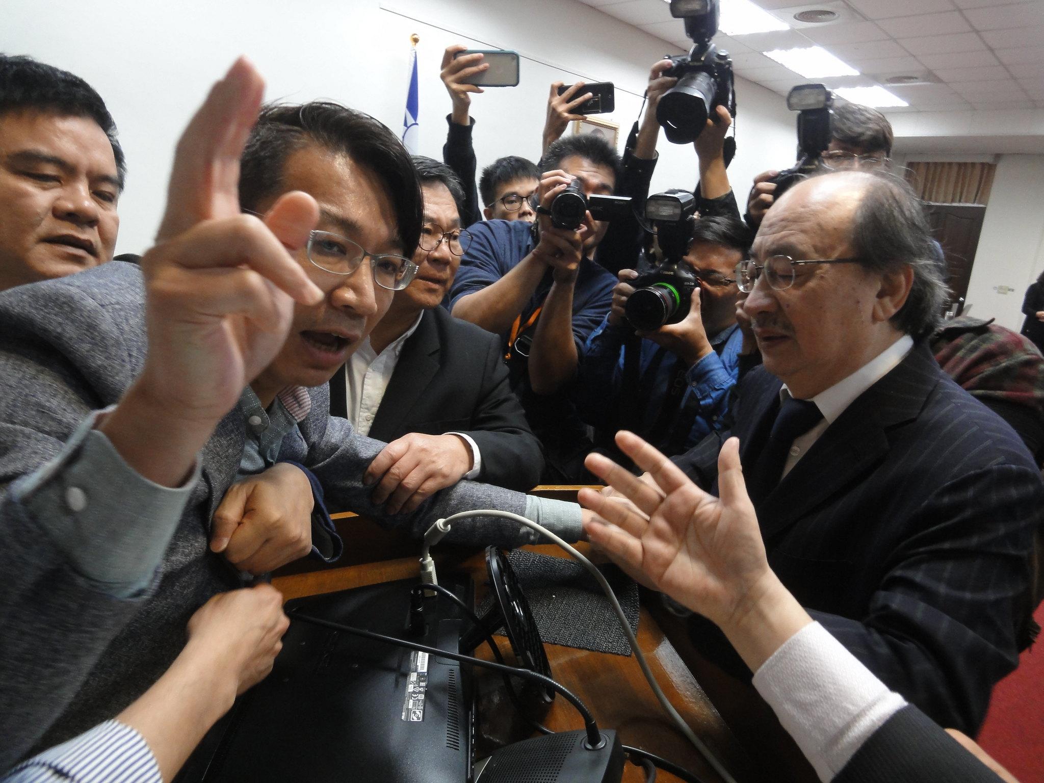 時代力量立委徐永明被拖離發言台。(攝影:張智琦)