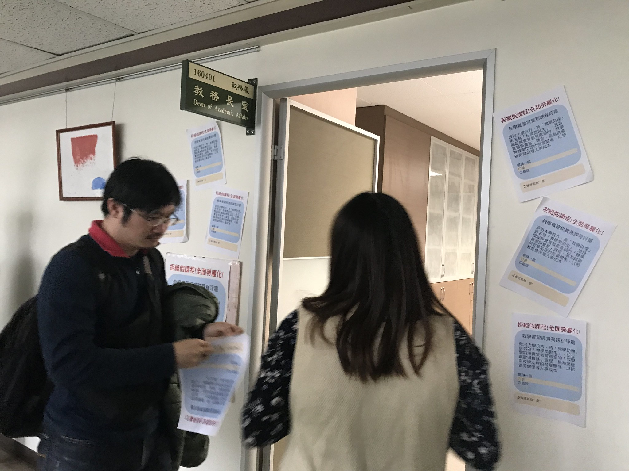 學生將諷刺政大兼任助理課後問卷的字條黏貼在教務長室的門口。(攝影:張宗坤)