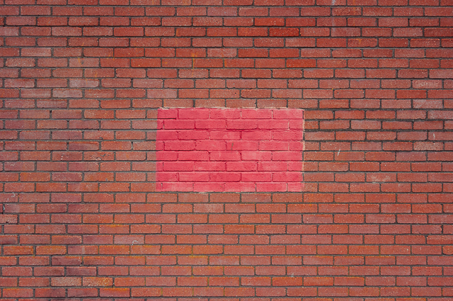 pink painted rectangle on brick wall