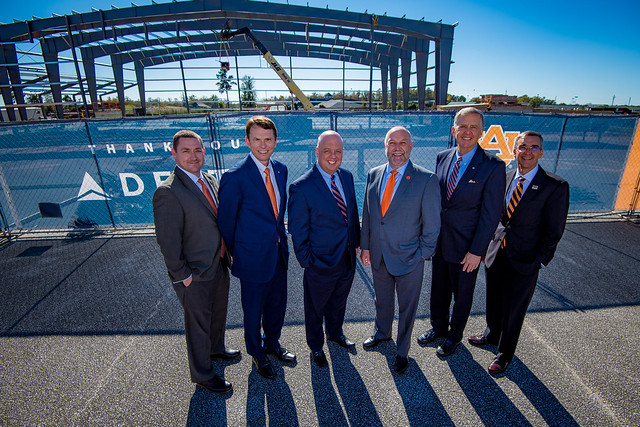 Six men, all dressed in suits, stand in front of a construction site at the Auburn University Regional Airport.