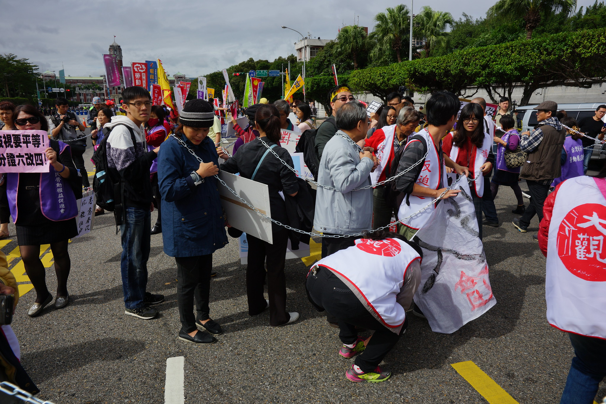 秋鬥遊行今年用鐵鍊纏身,在凱道上繞圈,象徵政府對人民的箝制。(攝影:王顥中)