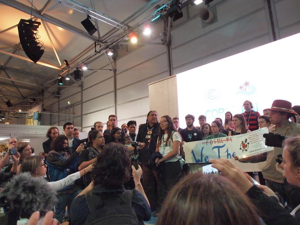 美國政府邊會進行時,運動人士在場外舉行記者會。圖中白衣女性是來自加州灣區的原住民伊莎貝兒·季季,屬於the Northern Cheyenne, Arikara, and Muskogee Creek tribes。