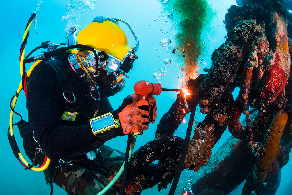 Navy Diver Performs Underwater Cutting Operations Using A