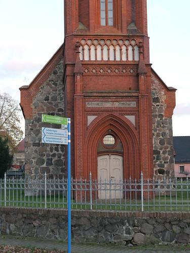 Richtungsschilder mit Entfernungsangaben vor der Dorfkirche aufgestellt