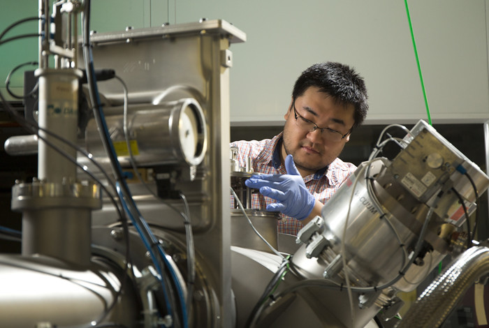 Researcher Di Chen loading nanolayered metal specimens for helium implantation into a Danfysik Research Ion Implanter at the Los Alamos National Laboratory Ion Beam Materials Laboratory. Chen is a Texas A&M University collaborator with Los Alamos scientists.