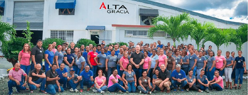 Workers at the Alta Gracia factory in Villa Altagracia, DR pose in front of their factory