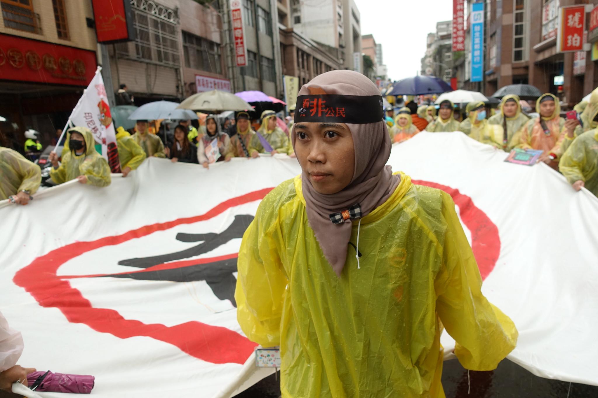 移工拉著「反奴」旗幟前進。(攝影:張智琦)