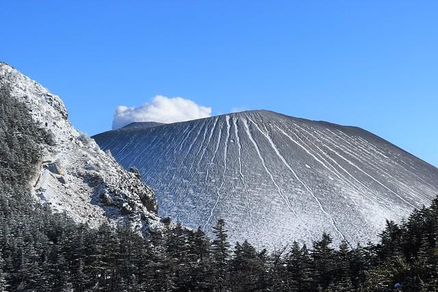 雪の浅間山と噴煙