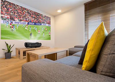 Epson's first ultra-short throw laser projector for homes, the ultra-short throw design of the EH-LS100 allows it to project at extremely close distances to a wall without the need for mounting on the ceiling, enabling easy installation and a seamless integration with the home décor.