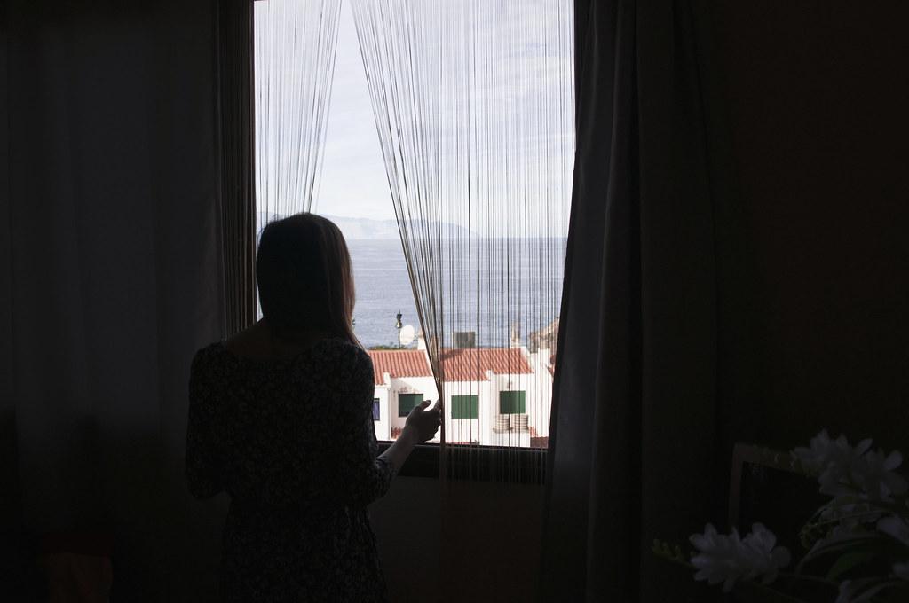 dziewczyna wyglądająca przez okno i rozsuwająca zasłony w Puerto de Santiago