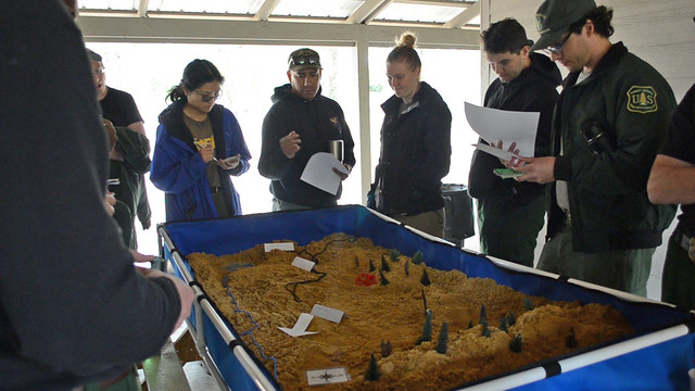 Wildland Firefighter Apprenticeship Program instructors use a sand table to teach and evaluate tactical decision-making skills.