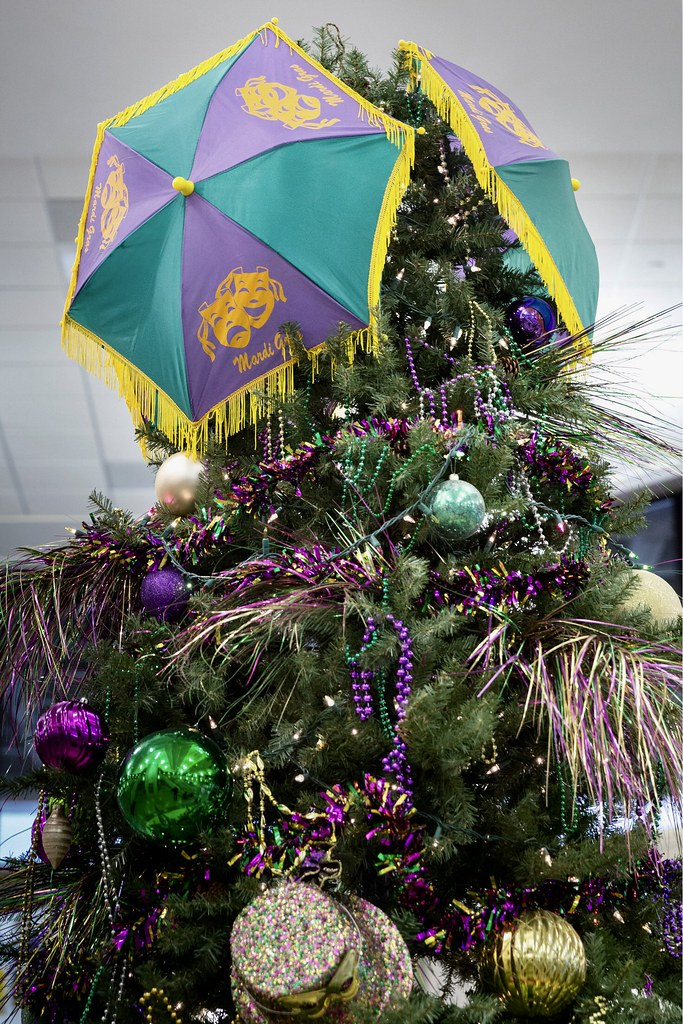 top of a mardi gras christmas tree decorated with purple justice green