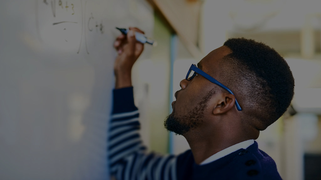 Photo of a male student writing mathematical calculations on a whiteboard.