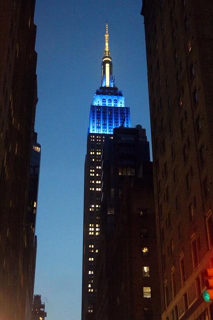 Empire State Building upplyst i gult & blått.