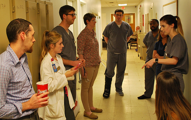 Students meet outside an exam room at the student-run free clinic in Mobile.