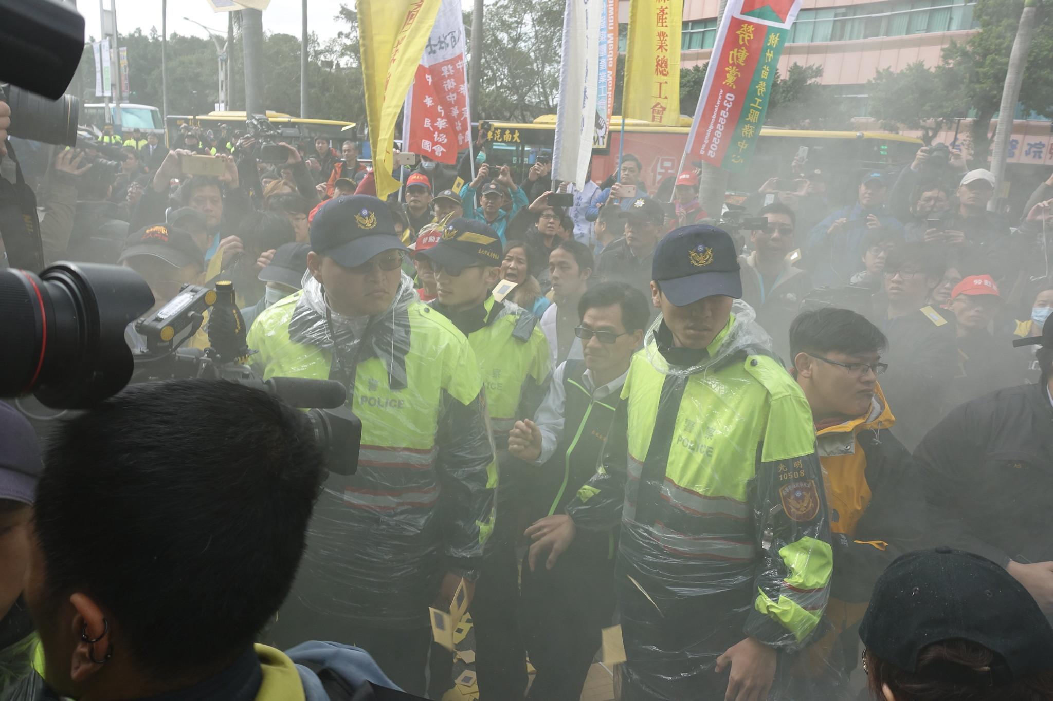 勞團一度燃燒煙霧彈,現場煙霧瀰漫,但立刻遭警方制止。(攝影:張智琦)