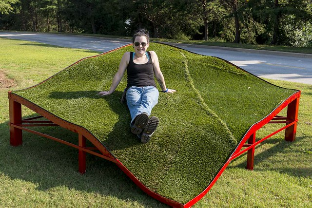 Stacey Rathert poses on a sculpture made of steel, artificial turf and ground cover.