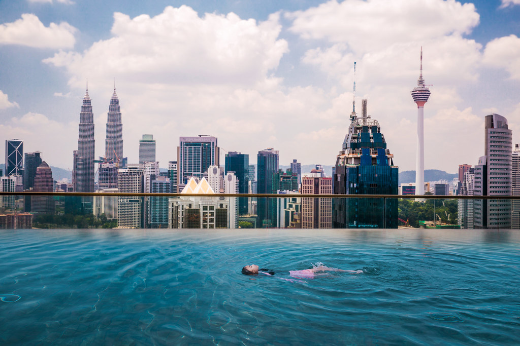 Asian girl swimming in roof top swimming pool in hotel