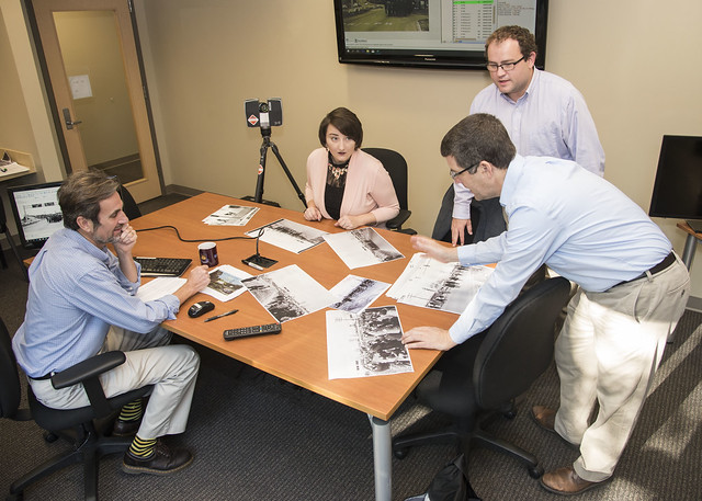 A team at Auburn University analyzes old photos around a table as they work to create a digital experience of Bloody Sunday.