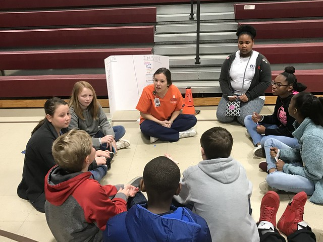 A group of elementary school children sit in a circle with an Auburn University nursing student.