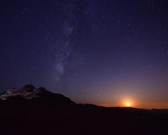 Las estrellas, la luna y la vía láctea al atardecer en Wadi Rum
