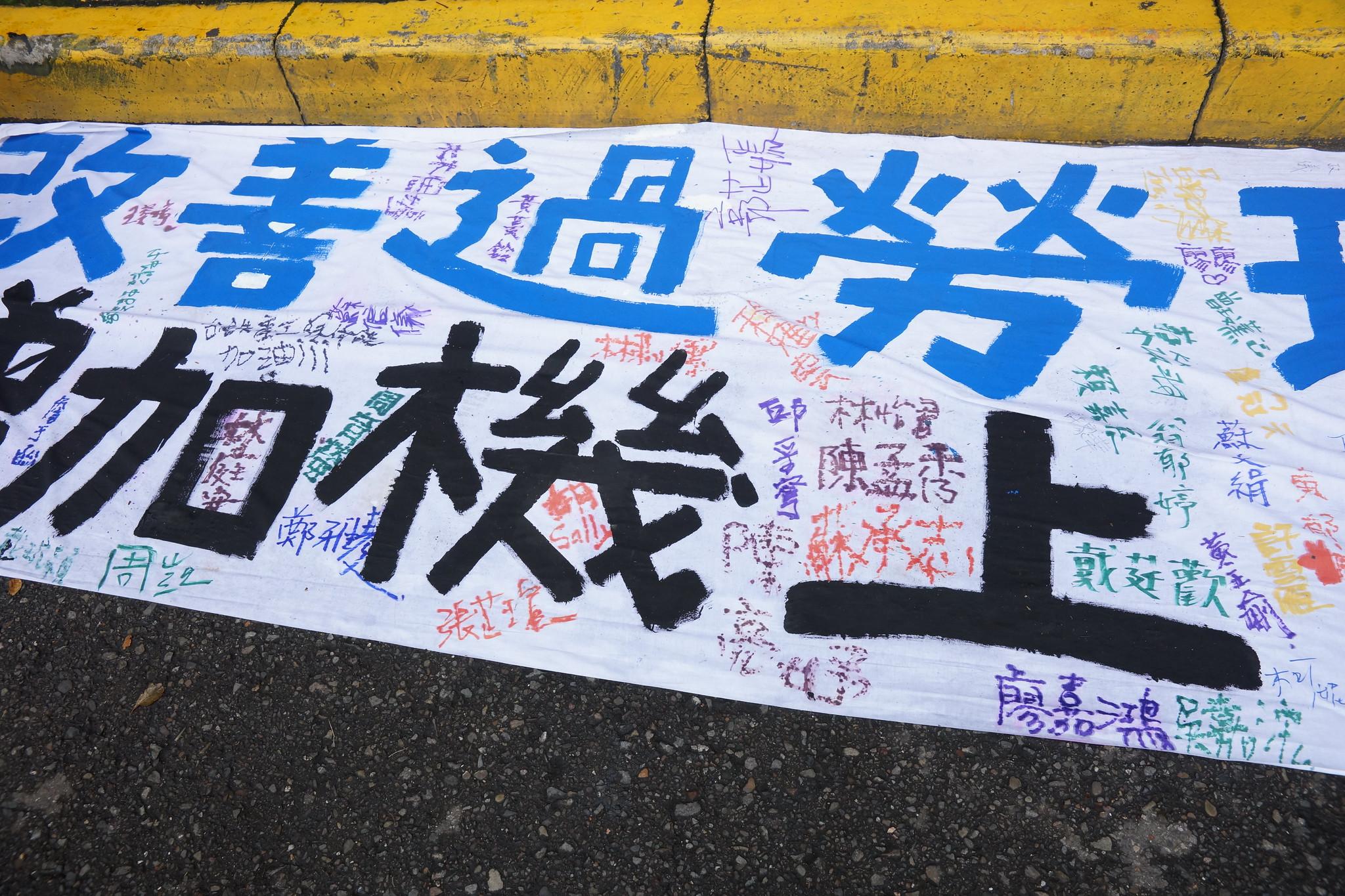 空服員在布條上連署簽名反對過勞航班。(攝影:王顥中)
