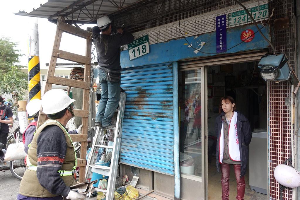 朱寧民女兒盯著工人修復朱宅的屋簷。(攝影:張智琦)