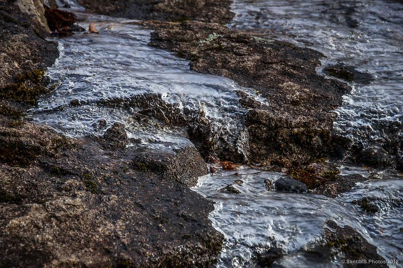 Corriente de agua parcialmente helada sobre una roca