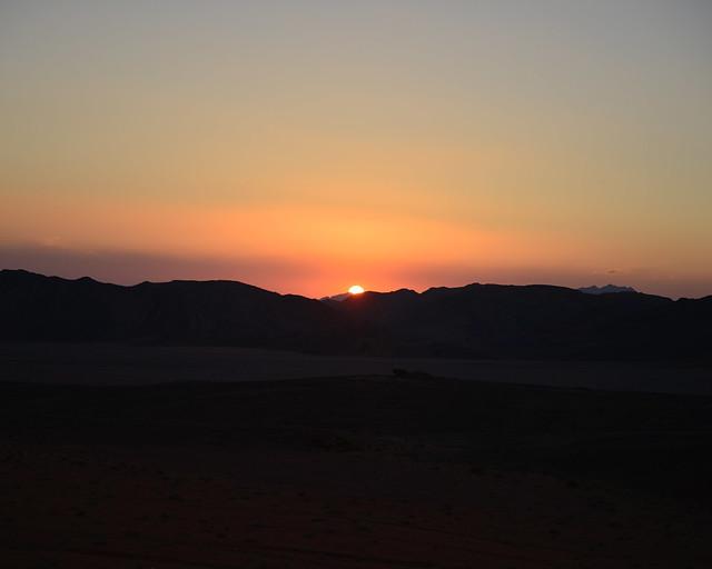 Silueta del sol tras las montañas de Wadi Rum