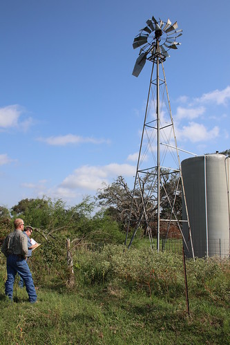 Stephen Diebel surveying windmill damage with NRCS employee