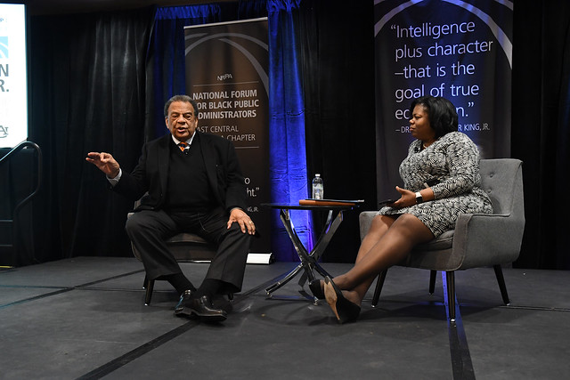 Civil rights activist Andrew Young joined Auburn University's Associate Provost and Vice President of Inclusion and Diversity Taffye Benson Clayton sit on chairs on stage during the MLK Scholarship Breakfast
