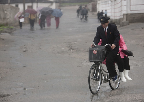 North Korean student giving a lift to a woman on his bicycle, North Hwanghae Province, Kaesong, North Korea | by Eric Lafforgue