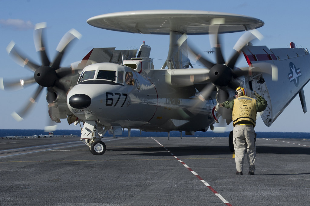 ... Sailor directs an E-2C Hawkeye on the flight deck of USS Harry S.