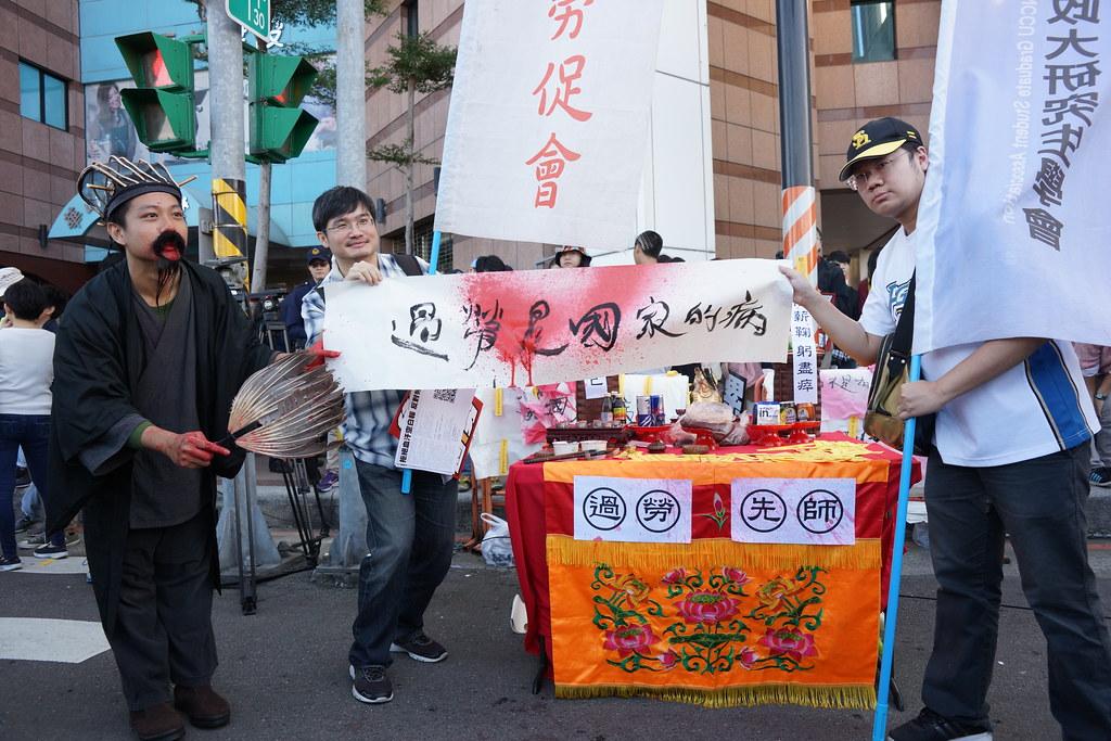"""1223""""反《劳基法》修恶游行""""在民进党部前集合,参与群众扮成""""过劳先师""""吐血表达抗议。(摄影:王颢中)"""