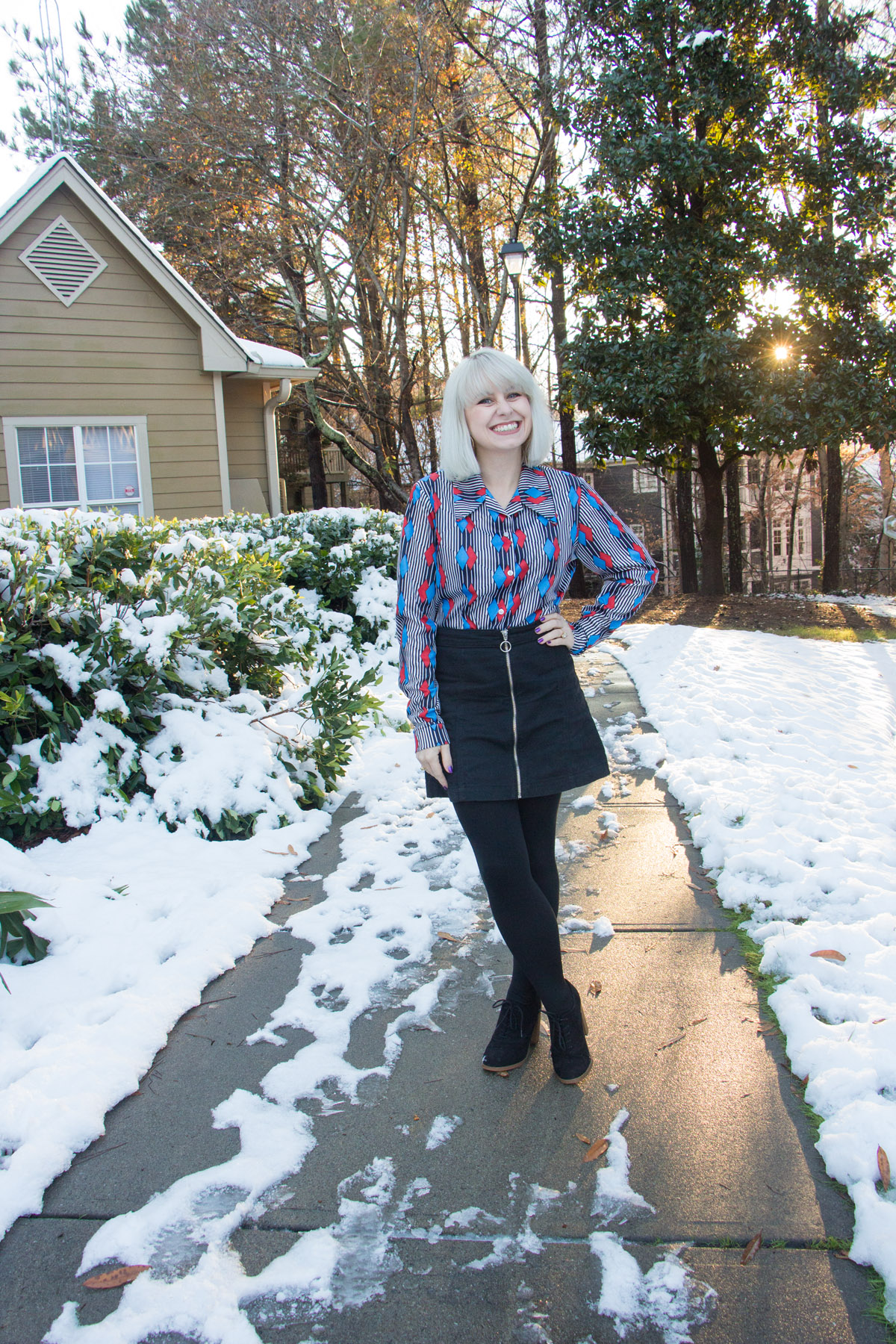 70s button down geometric blouse with black denim zip up skirt and platinum blonde hair
