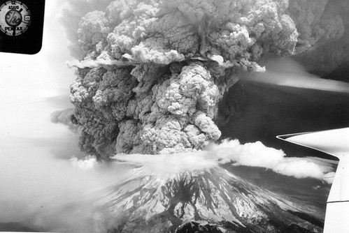 Grayscale image shows Mount St. Helens in eruption, taken from the air. The Plinian eruption column fills the sky and boils away in a wall to the north, toward the upper left of the photo. Horizontal streaks of white cloud intersect the column at the crater and higher up. The wing of the plane is visible at the bottom right.