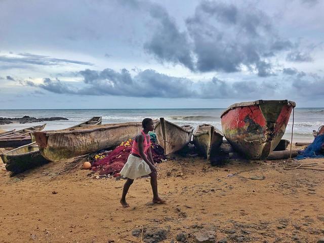 Mujer caminando entre barcos de pesca en Morro Peixe (norte de la isla de Santo Tomé)