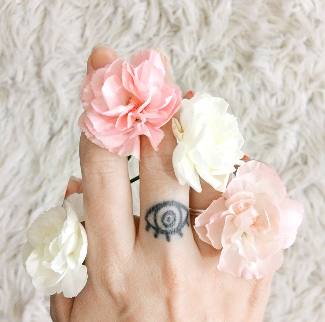 pink and white carnations between fingers