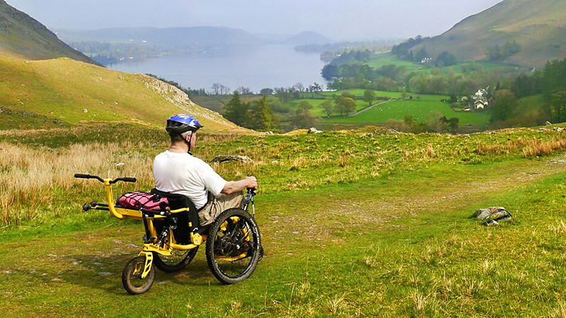 A man uses the Mountain Trike to traverse a path overlooking a lake surrounded by green rolling hills