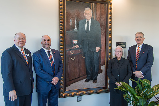 Christopher B. Roberts, Steven Leath, Dorothy Davidson, and Michael DeMaioribus stand next to a recently unveiled portrait of Julian Davidson.