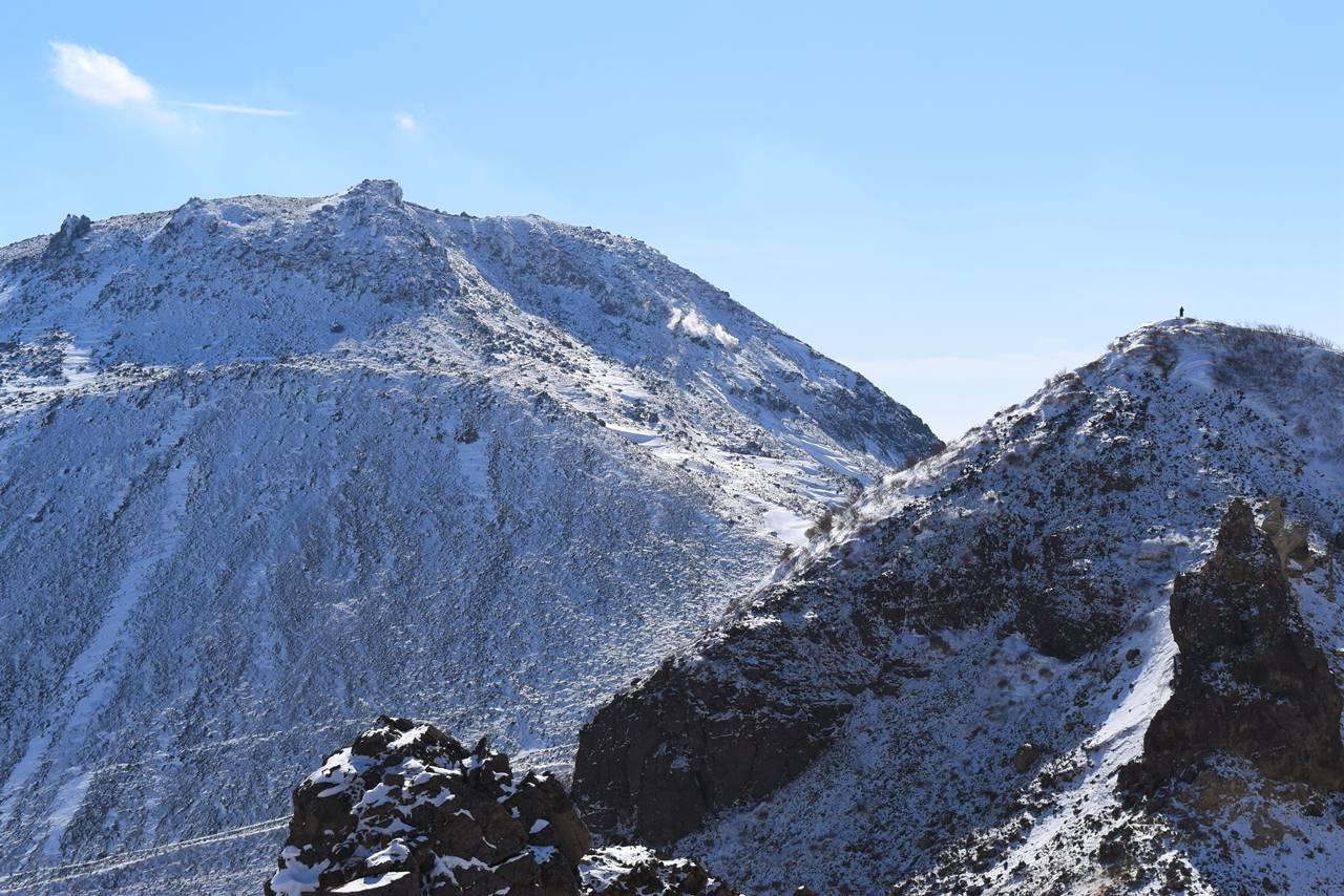 剣ヶ峰に立つ登山者と茶臼岳