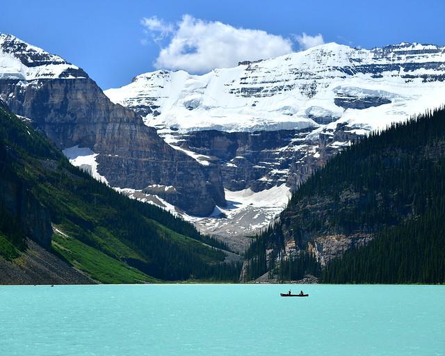 El lago Louise rodeado de montañas nevadas y una barca remando en él