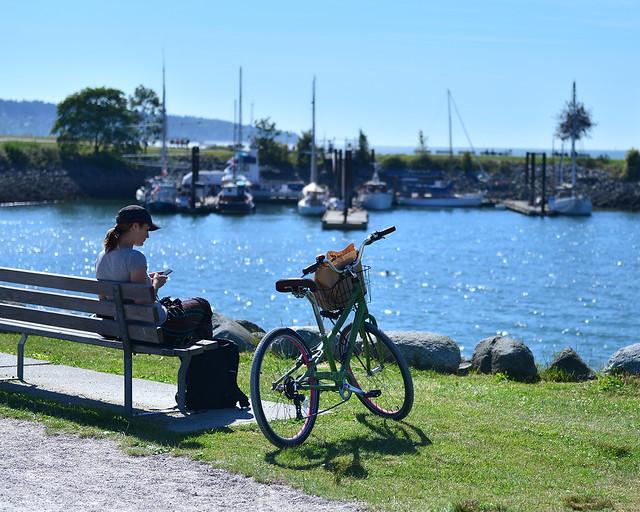 Mujer descansando con su bicicleta en Vancouver en un día soleado